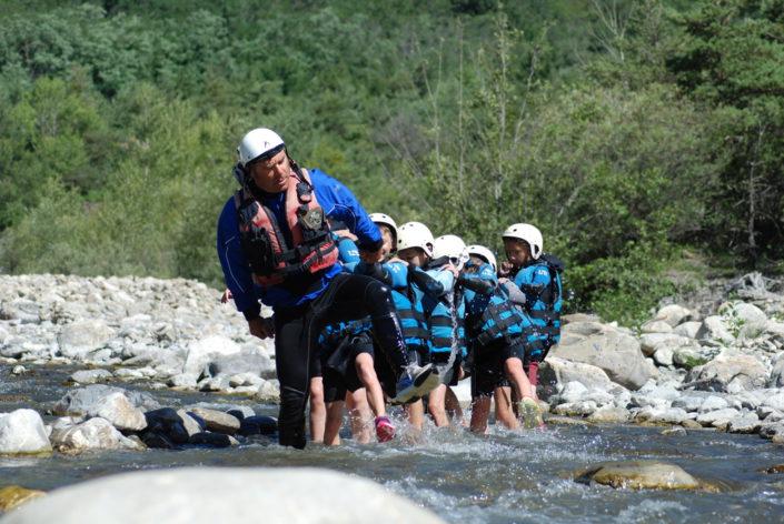 Gus fait la chenille avec un groupe d'enfants lors d'une pause sur la descente en raft