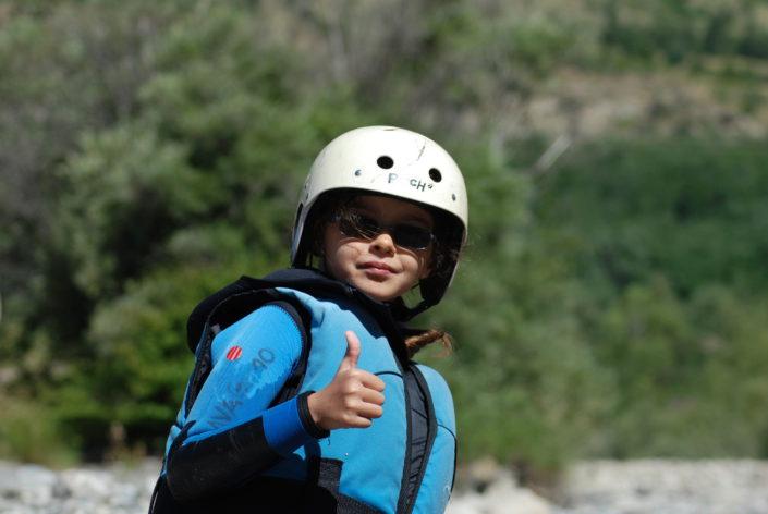 Une fillette montre qu'elle est contente de participer aux activités de La Vague Rafting