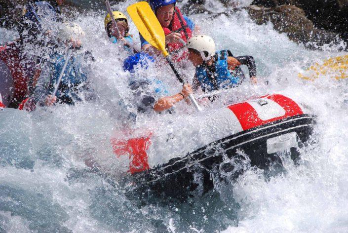 Les participants se font éclabousser à la vague du Rabioux lors d'une descente en rafting